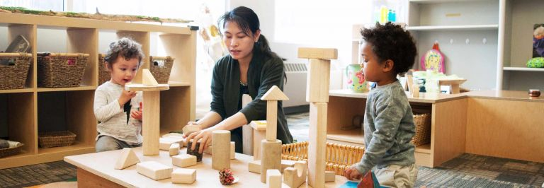 children and child care professional playing with building blocks